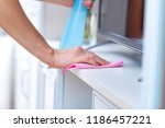 a young woman wipes the dust... | Shutterstock . vector #1186457221