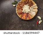 Dried Seafood Mix with Squid, Mussels, Tuna, Herring, Anchovies, Mackerel, Trout, Salmon on a Round Plate Top View. Cured Dehydrated Fish Fillet as Beer Snack Nice Serving on Black Stone Background