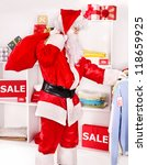 Santa Claus in clothing store. Christmas sale. - stock photo