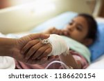 mother's hand is holding her... | Shutterstock . vector #1186620154