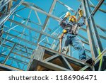 Steel Construction House Building and the Caucasian Contractor with Walkie Talkie in Hand. Skeleton Frame System. Industrial Theme. - stock photo