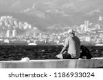 a man is sitting at the seaside ... | Shutterstock . vector #1186933024