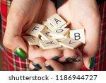 hands holding random alphabet... | Shutterstock . vector #1186944727