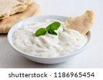 tzatziki in white ceramic bowl... | Shutterstock . vector #1186965454