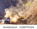 Small photo of Excavator and truck for construction site. Excavation is the process of moving earth, rock or other materials with tools, equipment or explosives. It includes earthwork, trenching, wall and tunneling.