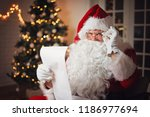 santa claus reading from a long ... | Shutterstock . vector #1186977694