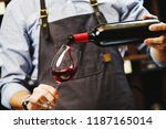 male sommelier pouring red wine ... | Shutterstock . vector #1187165014