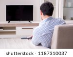 young man watching tv at home   Shutterstock . vector #1187310037