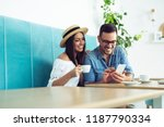 happy young couple sitting at... | Shutterstock . vector #1187790334