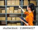 Small photo of e-shop female employee is counting the boxes on the shelf to make sure the amount of goods is right