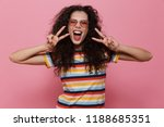 Small photo of Image of happy cute young woman posing isolated over pink background make peace gesture.