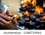 a person lights a candle in a... | Shutterstock . vector #1188719041