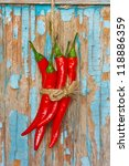 Red chili handing with rope on an old blue board. - stock photo