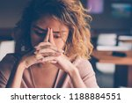 Small photo of Closeup of sad young Asian woman at cafe leaning head on clasped hands and staring into vacancy. Tired freelancer feeling burnout. Stress and bad news concept
