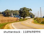 Country road winding through farmland in southern Wisconsin, USA, on a sunny morning early in autumn