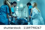 Small photo of Emergency Department: Doctors, Nurses and Surgeons Move Seriously Injured Patient Lying on a Stretcher Through Hospital Corridors. Medical Staff in a Hurry Move Patient into Operating Theater.