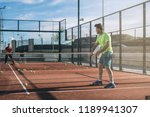 man playing padel in a orange... | Shutterstock . vector #1189941307