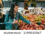 young woman picking apples in... | Shutterstock . vector #1190010367