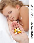 Hand giving lots of pills for a sick little girl - focus on hand - stock photo