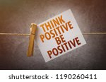 Small photo of Think positive be positive paper note attach to rope with clothes pins