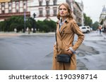 Young attractive woman in trench coat with little black cross bag dreamily looking in camera spending time on cozy city street