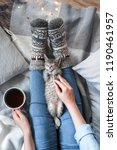 Stock photo a girl in knitted socks sits on a blanket holds her hand a cup of coffee and a kitten 1190461957