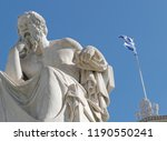 Small photo of Socrates the ancient philosopher and greek flag with vibrant blue sky background