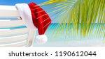 santa claus hat on sunbed near...   Shutterstock . vector #1190612044
