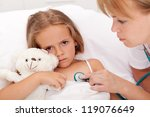 Health professional checking on sick little girl laying in bed - closeup - stock photo