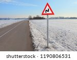 Small photo of Double bend ahead right then left road sign in winter land. Warning on the way. Double bend signification. Warning traffic sign next to the winter route. Drive trough the fields with double bend sign