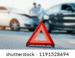 Small photo of Two men reporting a car crash for the insurance claim,main focus on red triangle