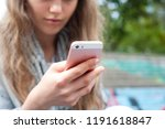 young girl using a phone | Shutterstock . vector #1191618847