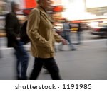 A motion blur of a woman and others walking down a busy Manhattan street. - stock photo