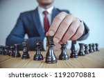 Small photo of Retro style image of a businessman with clasped hands planning strategy with chess figures on an old wooden table.