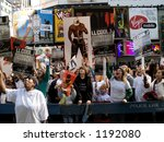 A crowd of excited fans downstairs on the street in front of MTV displaying signs and screaming. - stock photo