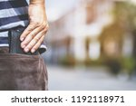 Confident man keeping wallet in the back pocket of his back pocket pants. savings money. - stock photo