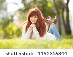 young woman walking in the park.... | Shutterstock . vector #1192356844