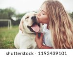 Stock photo frame with a beautiful girl with a beautiful dog in a park on green grass 1192439101