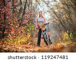 girl biking in autumn forest | Shutterstock . vector #119247481