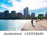 woman riding bike along lake...   Shutterstock . vector #1192518634
