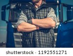 Truck Driver Workhorse. Caucasian Men in Front of His Vehicle with Crossing Arms. Powerful Transportation Industry Concept. - stock photo