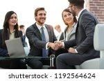 two colleagues handshaking... | Shutterstock . vector #1192564624
