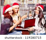 Women in santa hat drinking champagne in cafeteria. - stock photo