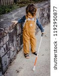 Small photo of Blind or Visually Impaired Child/Kid/Toddler/Preschooler/Boy Walking Through Neighborhood with Long White Cane, Exploring Concert Wall Ledge