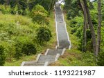 Long concrete stairway leading up a mountainside in densely forested on an overcast afternoon.
