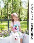 Stock photo beautiful little girl sitting on bench in park with her adorable white pomeranian dog 1193447071