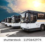 city buses in a row in a parking lot under a sunny, cloudy sky - stock photo