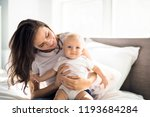mother with baby on bed having... | Shutterstock . vector #1193684284