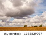 Small photo of Large clouds loom over farm buildings near cornfield on a morning early in autumn in northwestern Illinois, USA, for rural, agricultural, and meteorological themes
