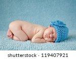 A Newborn Baby Is Wearing A...